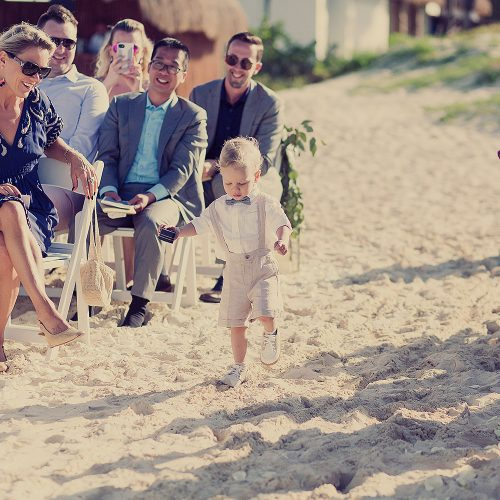 ring bearer walking down sand aisle.