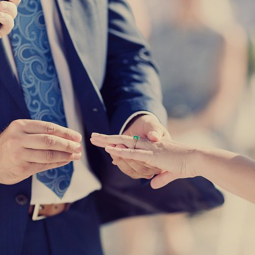 Groom putting on ring during wedding ceremony.