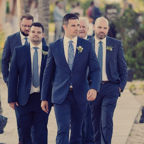 Groom walking with groomsmen.