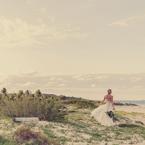 Back of bride with walking on beach.