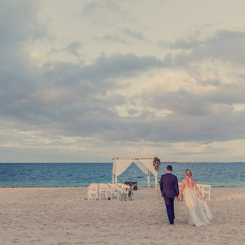 Bride and groom walking towards wedding ceremony location at Finest Playa Mujeres