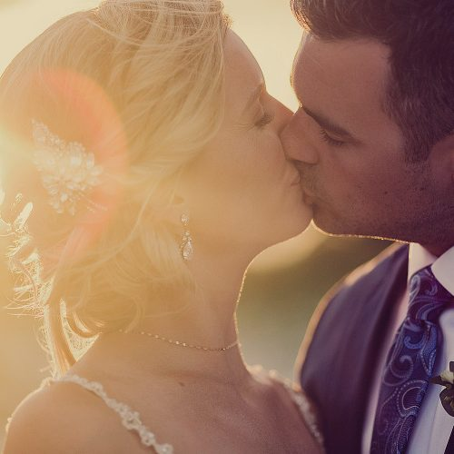 Bride and groom kissing with sunset.