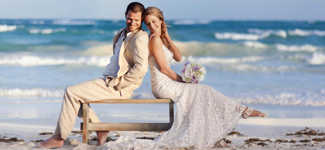 Bride and groom on bench on beach at Cancun wedding