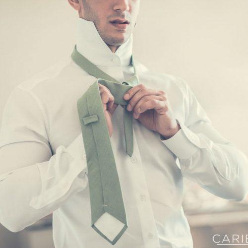 Groom putting on tie.