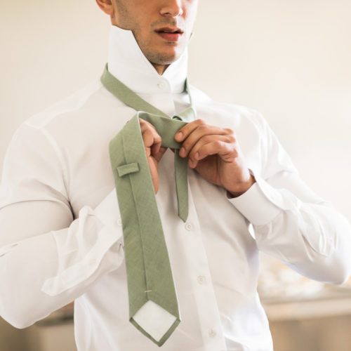 Groom doing up tie.