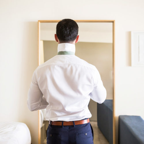 Groom getting ready in hotel room.
