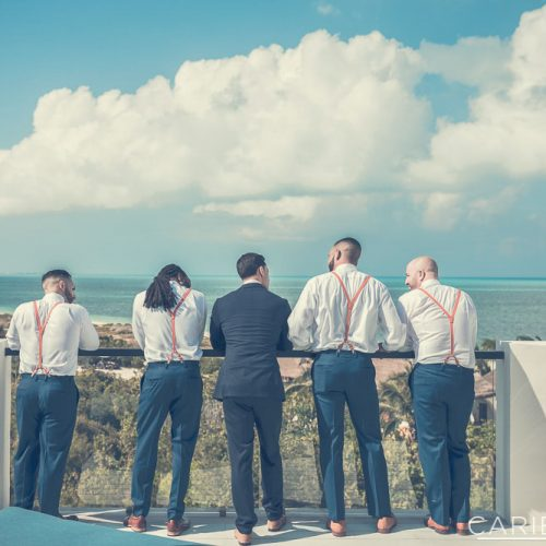 Groomsmen looking out at ocean at The Finest Playa Mujeres resort