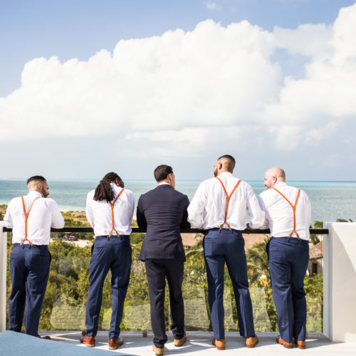 Groomsmen looking off to ocean on rooftop deck at Finest Playa Mujeres