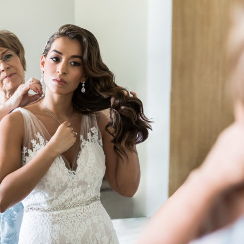Mother of bride helping bride get ready in front of mirror
