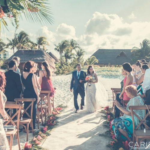 Bride walking down the aisle at beach wedding.