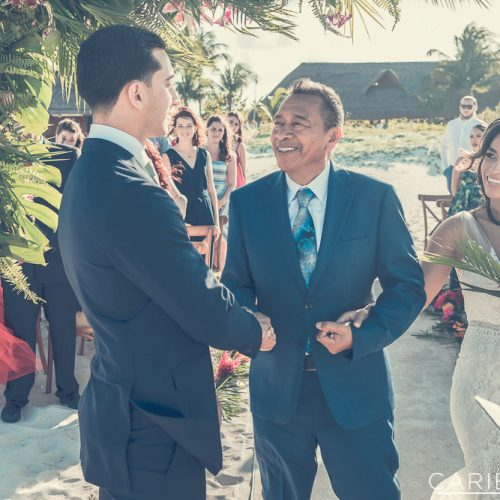 Bride and groom with father at wedding ceremony