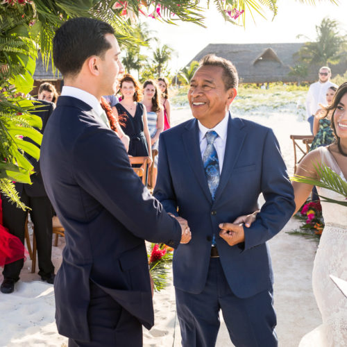 Groom shaking hands with father of bride at wedding ceremony.