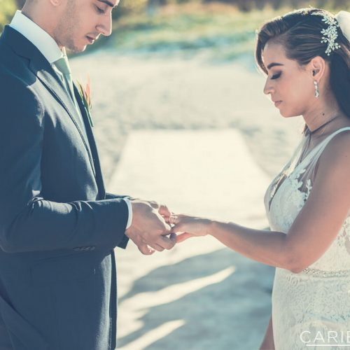 Bride and groom exchanging rings at The Finest Playa Mujeres resort
