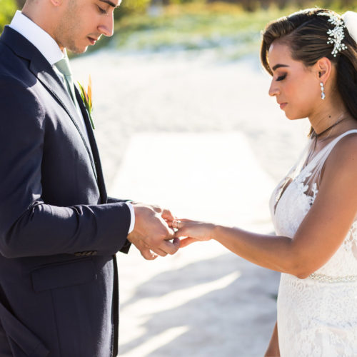 Bride and groom exchanging rings during beach wedding ceremony.
