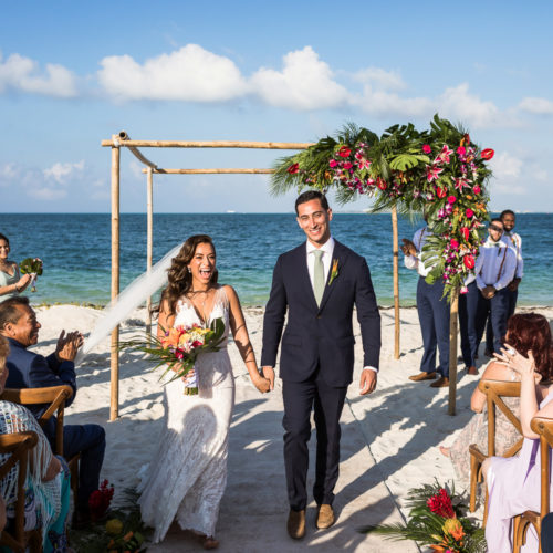 Bride and groom walking after beach wedding ceremony