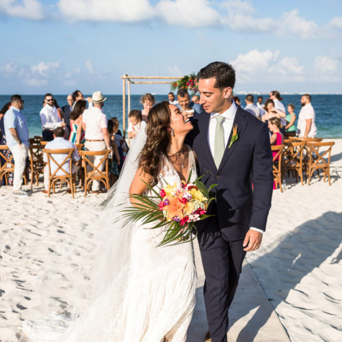 Bride and groom shortly after wedding ceremony on beach.