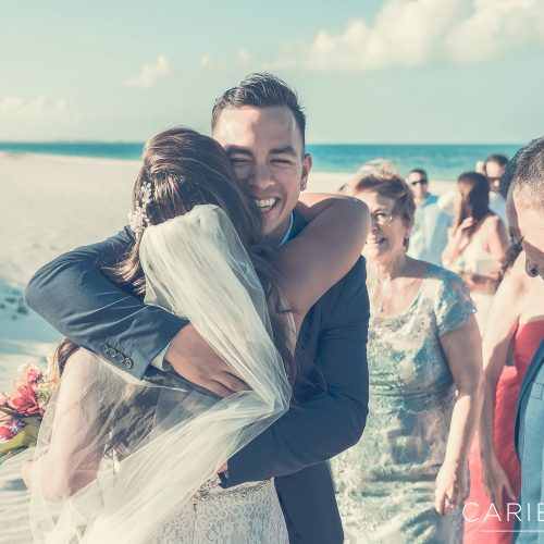 Bride hugging a guest after beach wedding at Finest Playa Mujeres Wedding, Cancun Mexico