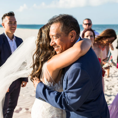 Bride hugging father after wedding.