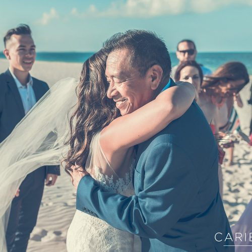 Bride hugging father after beach wedding at Finest Playa Mujeres, Cancun Mexico