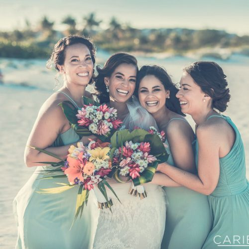 Bridesmaids laughing on beach.