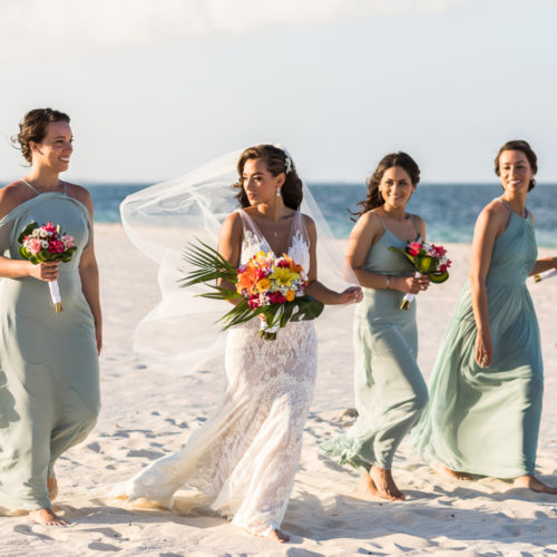 Bridesmaids walking on beach at Finest Playa Mujeres