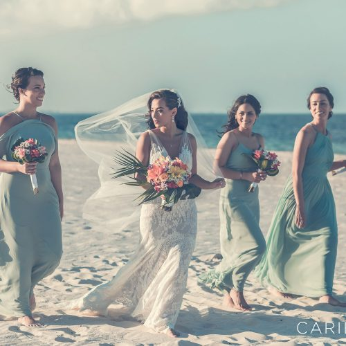 Bridesmaids walking on beach after wedding at Finest Playa Mujeres, Cancun Mexico