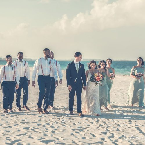 Entire wedding party waking on beach at Finest Playa Mujeres, Cancun Mexico