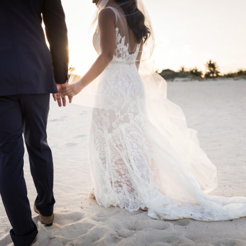 Bride and groom holding hands walking on beach.