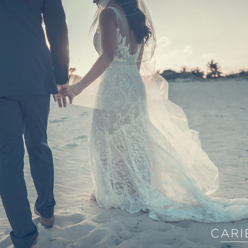Close up of hands as bride and groom walk on beach
