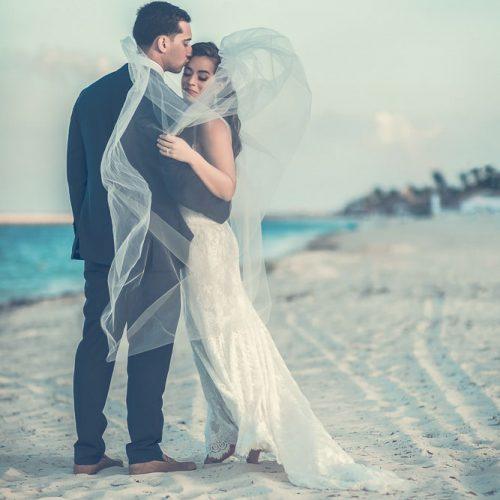 bride and groom looking away on beach.