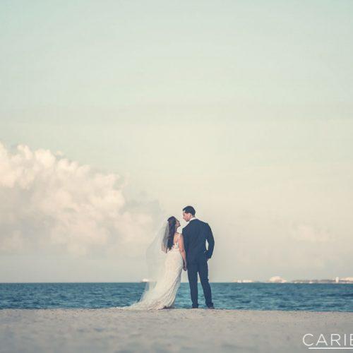 Bride and groom looking away at ocean.