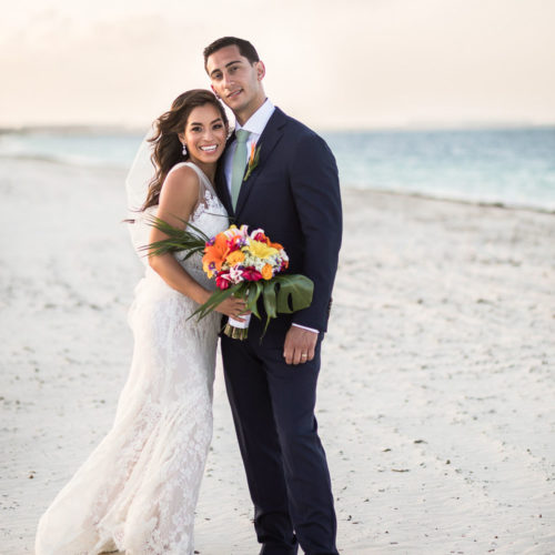 Portrait of bride and groom on beach.