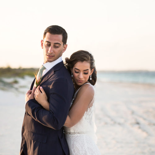 Bride hugging groom from behind on beach.