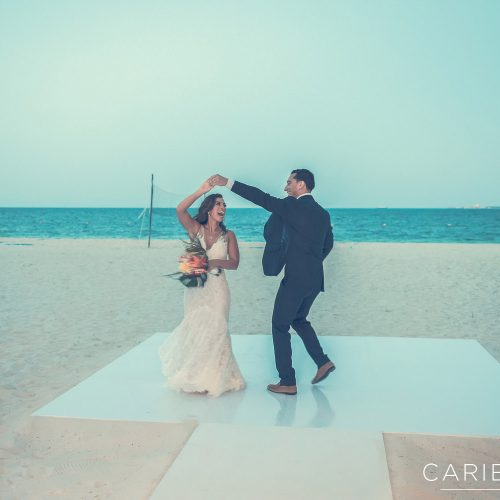 Bride and groom dancing on beach dance floor