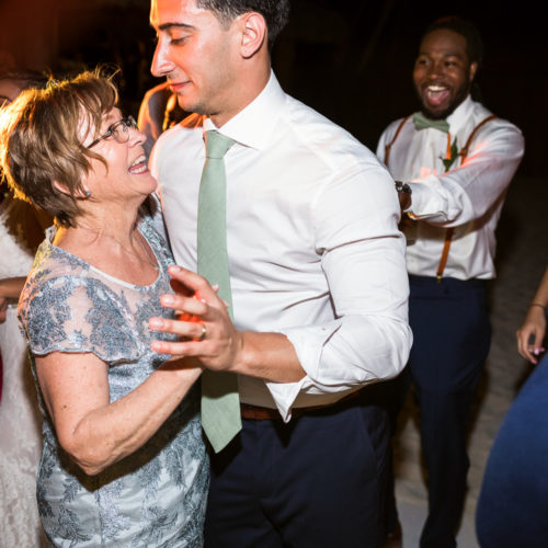 Mother dancing with groom at wedding reception.
