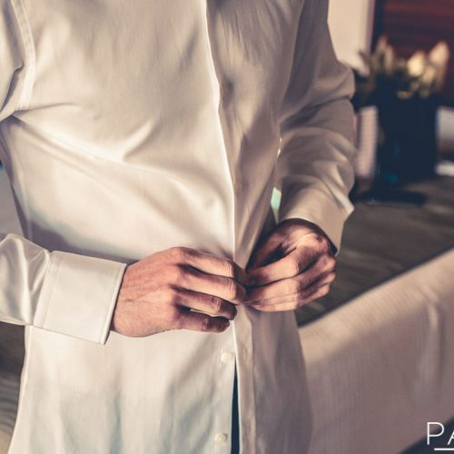 Detail of groom doing up shirt before wedding