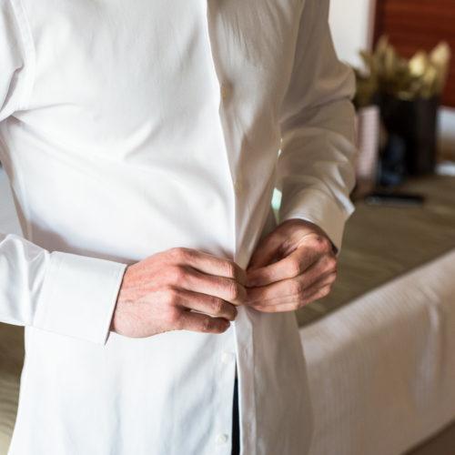Close up of groom doing up shirt at Secrets Playa Mujeres resort
