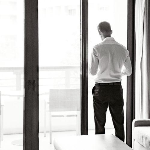 Groom looking out window before wedding at Secrets Playa Mujeres resort