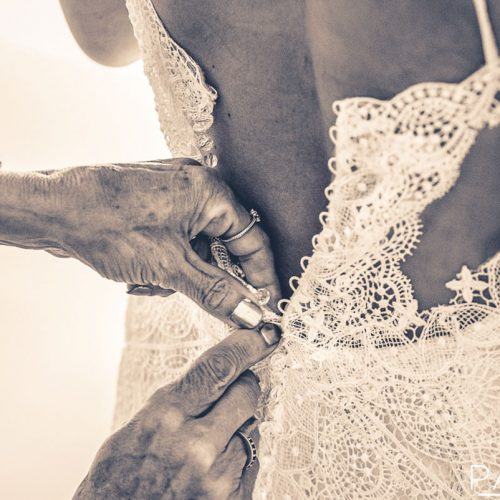 Detail of mother doing up brides dress.