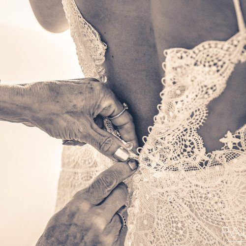 Detail of brides dress being done up.