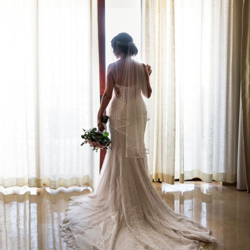 Bride looking out window before wedding ceremony at Secrets Playa Mujeres resort