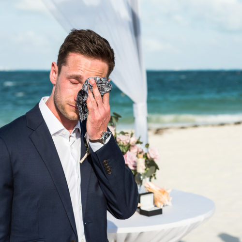 Groom crying while bride walks down aisle.