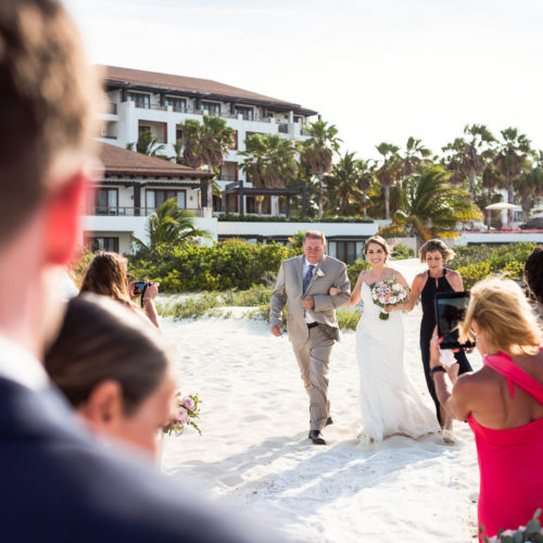 Bride walking down aisle at ceremony on the beach at Secrets Playa Mujeres resort