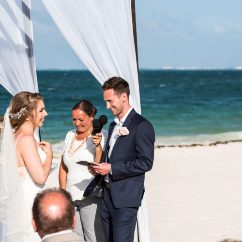 Bride and groom saying vows on beach at Secrets Playa Mujeres resort