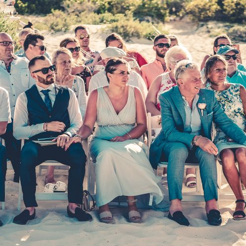 Parents of the bride and guests at wedding ceremony on beach at Secrets Playa Mujeres, Cancun Mexico