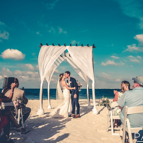 Bride and groom kiss at beach wedding at Secrets Playa Mujeres in Cancun Mexico