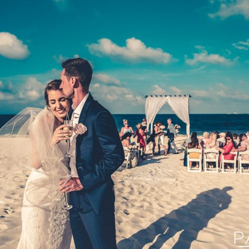 Bride and groom kiss after beach wedding at Secrets Playa Mujeres in Cancun Mexico