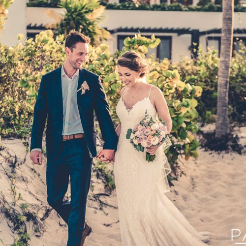 Bride and groom walk on beach with plants in background at Secrets Playa Mujeres in Cancun Mexico