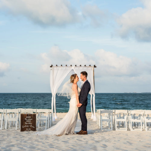 Bride and groom in front of ceremony location at Secrets Playa Mujeres resort
