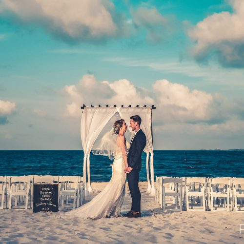 Bride and groom in front of wedding arch at Secrets Playa Mujeres, Cancun Mexico